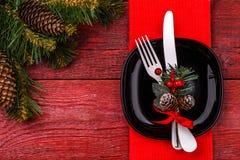 De plaats die van de Kerstmislijst met rood servet, zwarte plaat, wit vork en mes, verfraaide twijg plaatsen van maretak en Stock Afbeeldingen