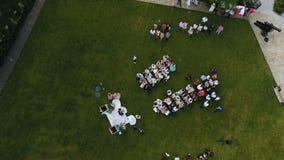 De plaats van de huwelijksceremonie met bruid en bruidegom, weg tussen gasten witte stoelen stock videobeelden
