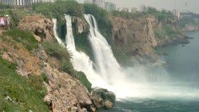 De plaats waar de toeristen, hoge mooie waterval, groene installaties en schuimend water gaan stock video