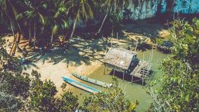 De plaatselijke bevolking onttrekt nieuwe plaats, Bamboehut en Boten op Strand in eb, Kabui-Baai dichtbij Waigeo Het westen Papua Royalty-vrije Stock Foto's