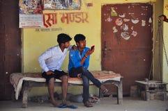 De plaatselijke bewoners controleren hun telefoons in Varanasi, India stock foto's