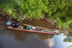 De plaatselijke bewoners drijven in traditionele papuan pirogue van een boomboomstam Stock Foto's