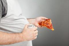 De plak van de de holdingspizza van de mens en ingeblikte drank stock afbeeldingen