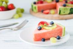 De plak van de watermeloenpizza met vruchten, witte houten achtergrond Stock Afbeelding