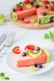 De plak van de watermeloenpizza met vruchten, witte houten achtergrond Royalty-vrije Stock Afbeeldingen