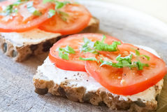 De plak van het graangewassenbrood met tomaat en ricotta Stock Foto's