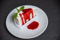 De plak van de rouwbandcake met aardbeisaus op witte plaat op donkere achtergrond royalty-vrije stock afbeelding
