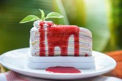 De plak van de rouwbandcake met aardbeisaus op witte plaat en aard groen achtergrond/Stuk cakeregenbogen stock afbeelding