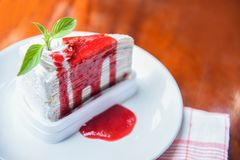De plak van de rouwbandcake met aardbeisaus op witte plaat op lijst/Stuk cakeregenbogen stock afbeeldingen