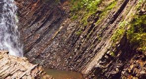 De plak van steen schommelt geologische achtergrond met een waterval Stock Foto