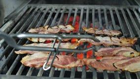 De plakken van bacon worden geroosterd, het vet van de baconafvoerkanalen van het gebraden bacon, de chef-kok in zwarte handschoe stock video