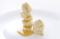De plakken van de banaan met honing Stock Afbeeldingen