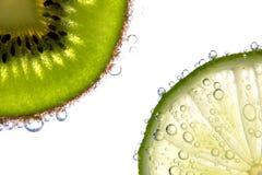 De plakken van de citroen en van de kiwi met bellen Stock Afbeelding