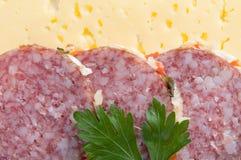 De plakken van de salami op kaasachtige achtergrond Royalty-vrije Stock Foto