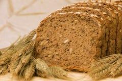 De plakken van het brood en natuurlijke graangewassen Stock Foto