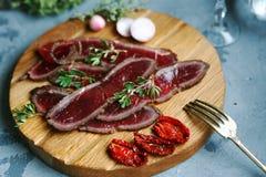 De plakken van vlees leggen het op een scherpe Raad met in de zon gedroogde tomaten Stock Foto
