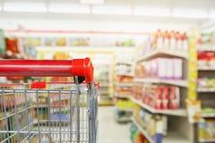 De plankenbinnenland van de gemakopslag met leeg supermarktboodschappenwagentje stock foto