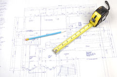 De plannen en het meetlint van de bouw Stock Afbeeldingen