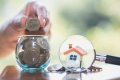 De planning van besparingengeld van muntstukken om een huisconcept, een hypotheek en een onroerende goedereninvestering te kopen  stock foto's