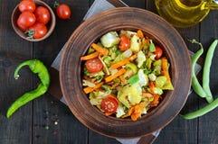 De plantaardige hutspot van kool, slabonen, wortelen, tomaten, uien, paprika's in een klei werpt Stock Afbeelding