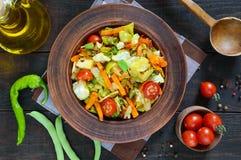 De plantaardige hutspot van kool, slabonen, wortelen, tomaten, uien, paprika's in een klei werpt Royalty-vrije Stock Foto