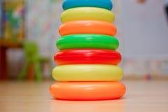 De plastic die piramide van kinderen, uit gekleurde ringen op gele achtergrond wordt samengesteld royalty-vrije stock afbeeldingen
