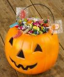 De plastic die pompoen van Halloween met suikergoed op houten lijst wordt gevuld - 1 Royalty-vrije Stock Fotografie