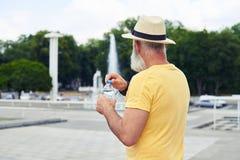 De plastic fles van de mensenholding water met stedelijke cityscape Royalty-vrije Stock Foto's