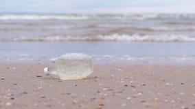 De plastic fles werd gebracht aan de kust op de zandige kust stock videobeelden