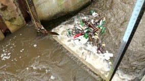 De plastic flessen en een andere knoeien het aanzetten van waterspiegel Het draaien van vuil water boven waterkering op kleine ri stock footage