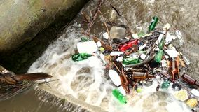 De plastic flessen en een andere knoeien het aanzetten van waterspiegel Het draaien van vuil water boven waterkering op kleine ri stock videobeelden