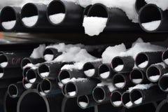De plastic pijpen in het gebeëindigde goederenpakhuis worden gestapeld in pakken in de sneeuw stock afbeelding