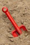 De plastic spade van het stuk speelgoed in zand Royalty-vrije Stock Foto's