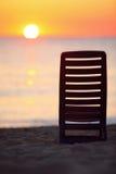 De plastic stoel bevindt zich op strand dichtbij overzees Royalty-vrije Stock Afbeeldingen