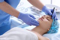 De plastic tekens van de chirurgentekening op vrouwelijke gezichtskliniek stock afbeeldingen