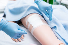 De pleegstudent werd opgeleid hoe te om zorgpatiënt te verwonden Zij praktizeert opleidend met Doll van patiënt, vóór behandeling Royalty-vrije Stock Fotografie