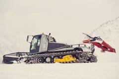 De ploeg van de sneeuw met een mens in zijn spoorketting Stock Foto