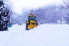 De ploeg van de sneeuw ontruimt de weg. Stock Foto