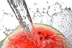 De plons van de watermeloen en van het water stock foto's