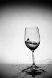 De plons van het glas en van het water Stock Afbeelding