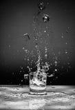 De plons van het water in glas die op wit wordt geïsoleerdl Royalty-vrije Stock Afbeelding