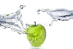 De plons van het water op groene appel die op wit wordt geïsoleerd Stock Afbeelding