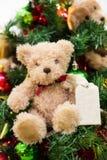 De pluche draagt met ornamenten en Kerstboomachtergrond Stock Fotografie