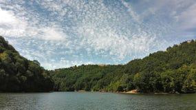 De pluizige wolken hangen het meer Stock Foto's