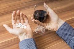 De poging van de zelfmoord De mens wil heel wat pillen met alcohol nemen Stock Foto's