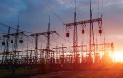 De polen van de hoge machtselektriciteit op stedelijk gebied Energievoorziening, distributie die van energie, energie, energietra royalty-vrije stock fotografie