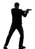 De politieagent die van de mensenmoordenaar kanon bevindend silhouet streven Stock Afbeelding