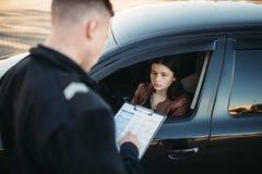 De politieagent in eenvormig schrijft boete aan vrouwelijke bestuurder stock foto's