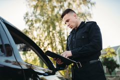 De politieagent in eenvormig schrijft boete aan vrouwelijke bestuurder stock afbeeldingen