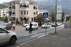 De politieagent leidt verkeer op de voetgangersoversteekplaats Budva, Montenegro stock fotografie